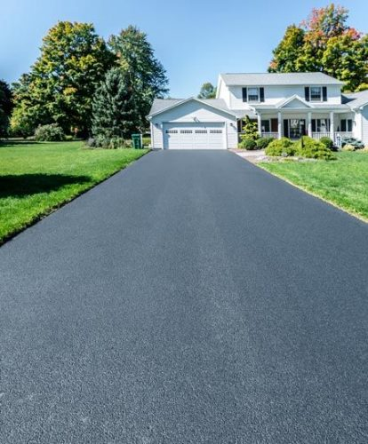 black-asphalt-driveway-in-front-of-white-home